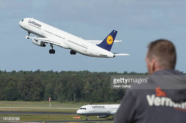 A man watches a Lufthansa passenger plane take off at Tegel Airport on September 6 2012 in Berlin Germany Lufthansa is bracing for a 24hour...
