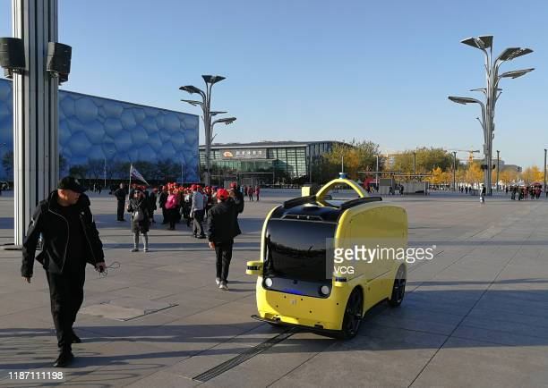 A man watches a Neolix autonomous driving retail near the Water Cube on Novemver 11 2019 in Beijing China
