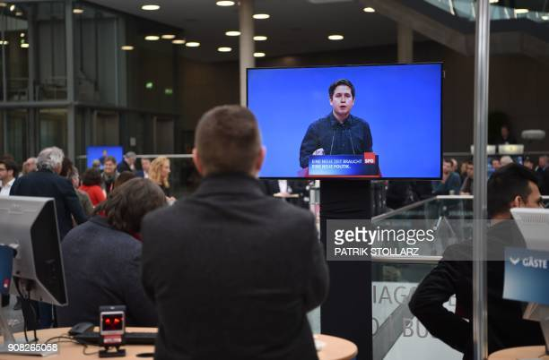 A man watches a screen displaying Kevin Kuehnert leader of Germany's social democratic SPD party's youth organisation 'Jusos' and opponent of the...