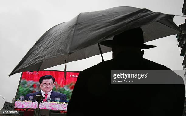 Man watches a screen showing Chinese President Hu Jintao delivering a speech during opening ceremony the 17th National Congress of the Communist...