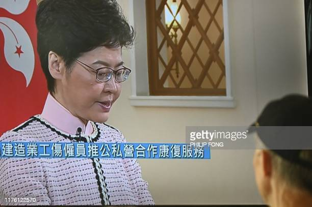Man watches a television broadcast showing Hong Kong's Chief Executive Carrie Lam delivering a recorded policy address after attempts to speak live...