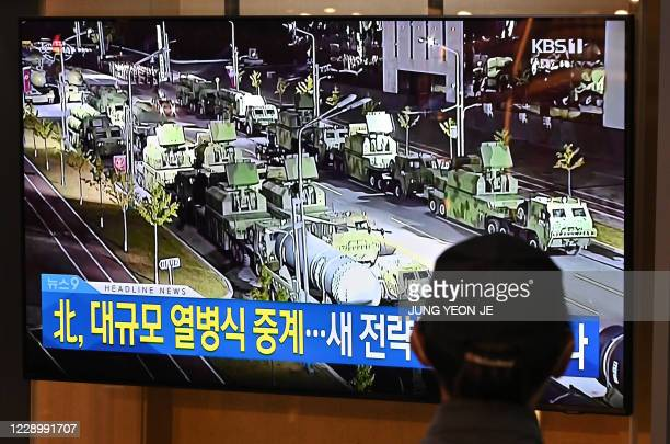 A man watches a television news broadcast of a military parade commemorating the 75th anniversary of North Korea's ruling Workers' Party held in...