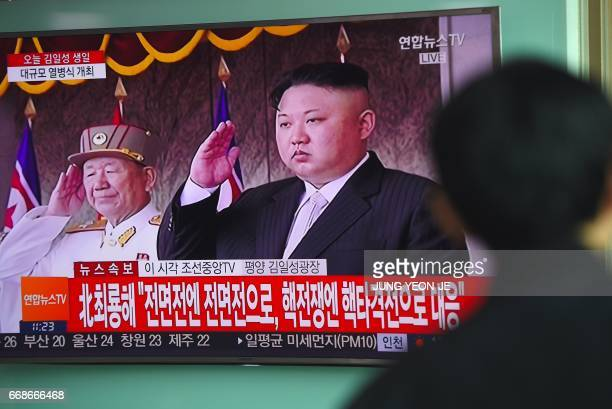 A man watches a television news broadcasting live footage of a parade to mark the 105th anniversary of the birth of North Korea's founder Kim IlSung...