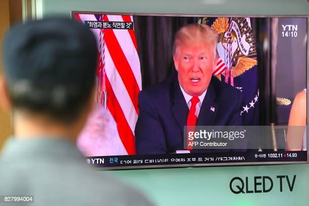 A man watches a television news programme showing US President Donald Trump at a railway station in Seoul on August 9 2017 President Donald Trump...
