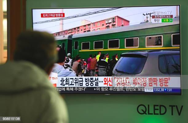 TOPSHOT A man watches a television news report about a suspected visit to China by North Korean leader Kim Jong Un at a railway station in Seoul on...