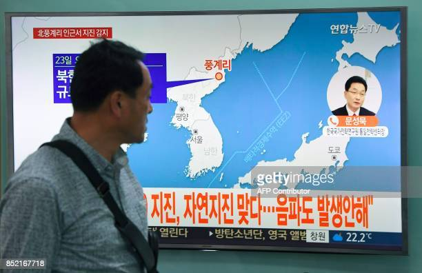 A man watches a television news screen showing a map of the epicenter of an earthquake in North Korea at a railway station in Seoul on September 23...