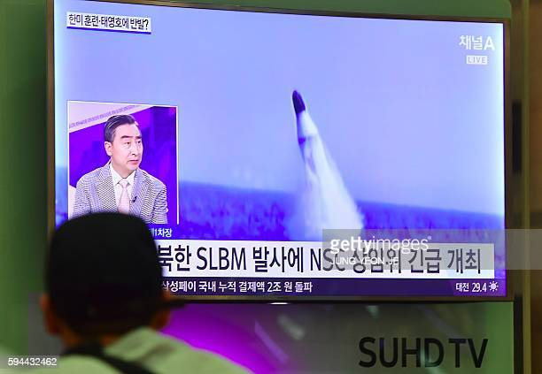TOPSHOT A man watches a television news showing file footage of a North Korean missile launch at Incheon airport west of Seoul on August 24 2016...