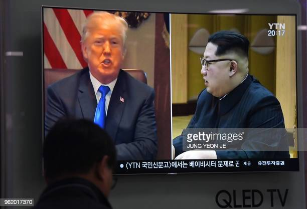 TOPSHOT A man watches a television news showing North Korean leader Kim Jong Un and US President Donald Trump at a railway station in Seoul on May 24...