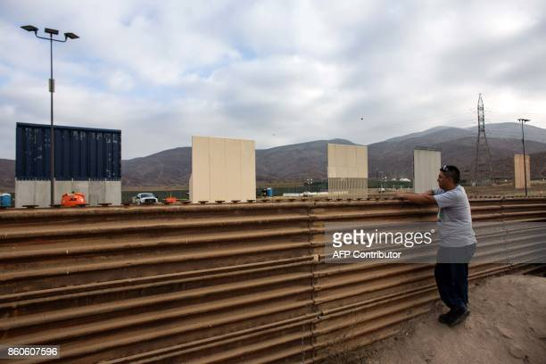 A man watches across the border from Tijuana Mexico on October 12 2017 a prototype of US President Donald Trump's USMexico border wall being built...