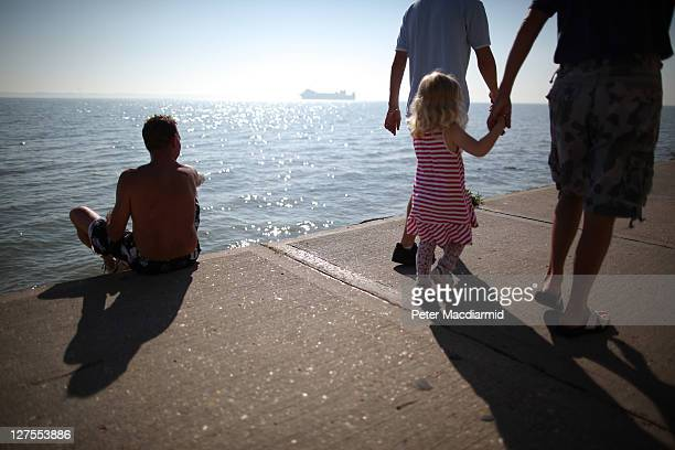 A man watches as a cargo ship heads to sea on September 29 2011 off Canvey Island England Much of the United Kingdom is enjoying a late spell of hot...
