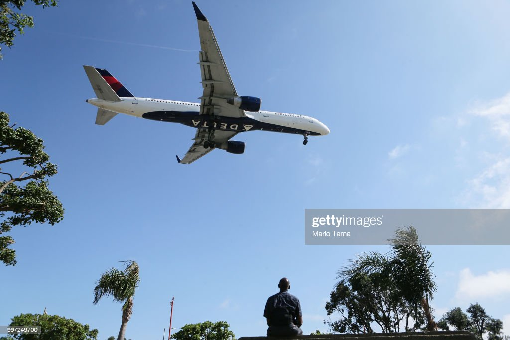 A man watches as a Delta Air Lines plane lands at Los Angeles International Airport on July 12, 2018 in Los Angeles, California. Delta announced today that it will increase fares by reducing the supply of seats in an effort to offset higher fuel prices.