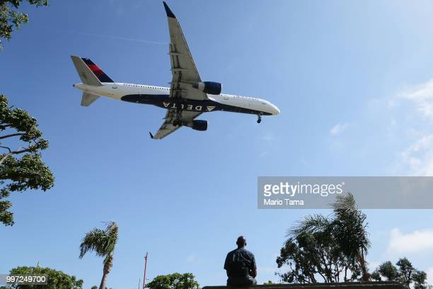 A man watches as a Delta Air Lines plane lands at Los Angeles International Airport on July 12 2018 in Los Angeles California Delta announced today...