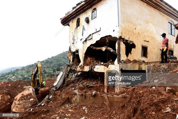 A man watches as a digger is used to clear mud and debris following the partial collapse of a hillside earlier in the week that swept away hundreds...