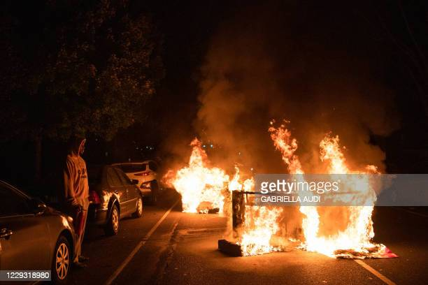 Man watches as a sofa, set on fire by protesters, burns in his street in West Philadelphia on October 27 during a demonstration against the fatal...