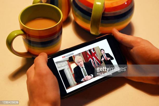 Man watches as Britain's Prime Minister Boris Johnson gives a televised message to the nation from 10 Downing Street in London, on his mobile phone...