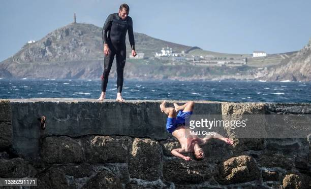 Man watches as his companion back flips as he jumps or tombstones off the harbour wall at Sennen Cove on August 23, 2021 near Penzance in Cornwall,...