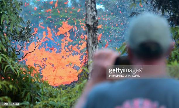 TOPSHOT A man watches as lava is seen sewing from a fissure in the Leilani Estates subdivision near the town of Pahoa on Hawaii's Big Island on May 4...