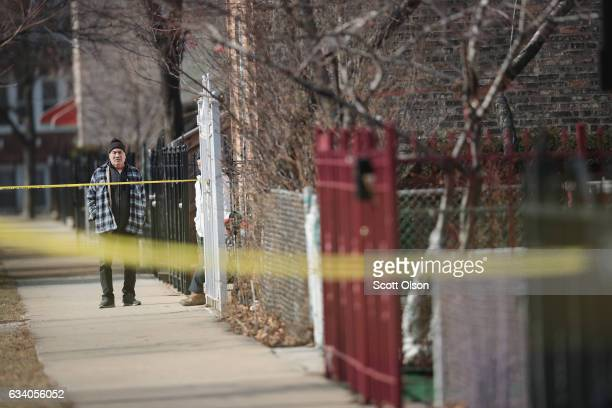 A man watches as police investigate the scene of a double homicide after two people were discovered shot inside an apartment on the morning of...