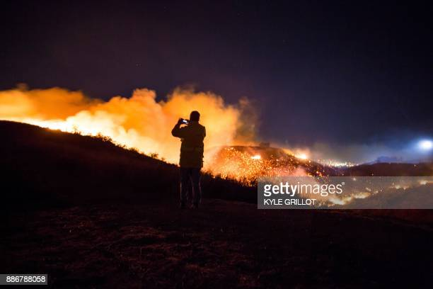 TOPSHOT A man watches as the Creek Fire burns along a hillside near homes in the Shadow Hills neighborhood of Los Angeles California on December 5...