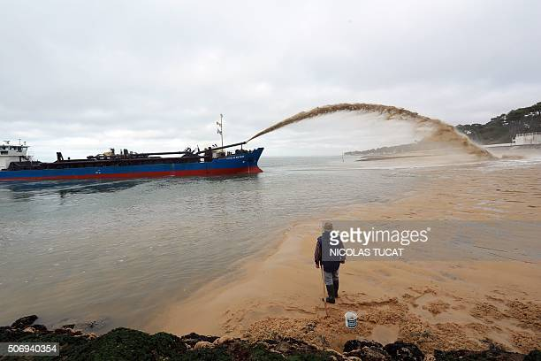 A man watches as the dredger 'Cotes de Bretagne' shoots sand onto a beach of PylasurMer in La TestedeBuch in Arcachon Bay The boat from Brittany...