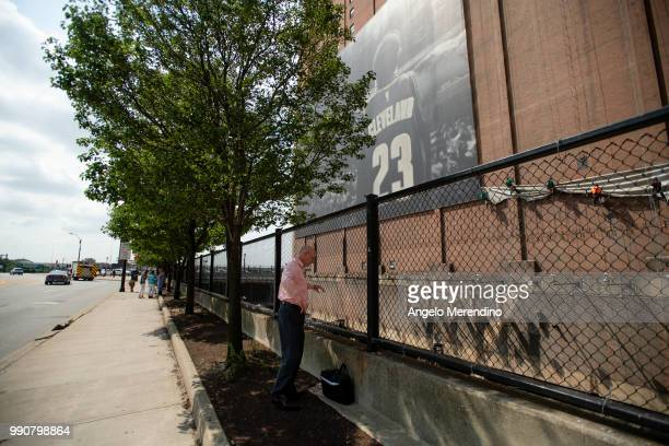 Man watches as workers remove the LeBron James banner from the Sherwin Williams building on the corner of Ontario and West Huron on July 3, 2018 in...