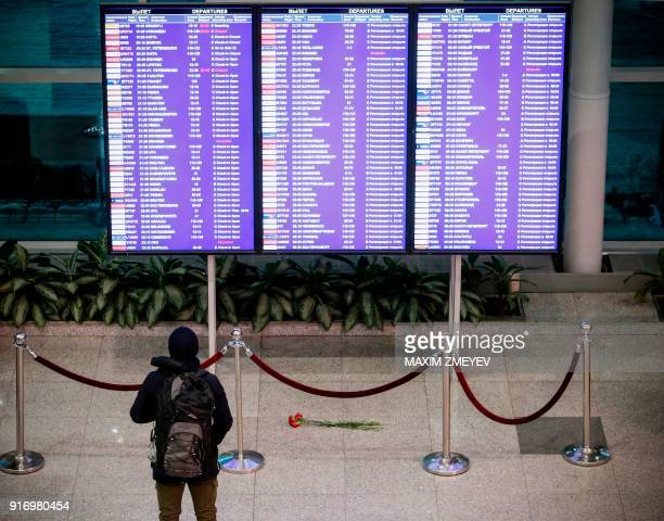 TOPSHOT A man watches at the flight schedule timetables next to flowers displayed in tribute to a plane crash victims at the Domodedovo International...