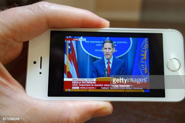 Man watches BBC live breaking news about the Ebola Outbreak on his iPhone 5S
