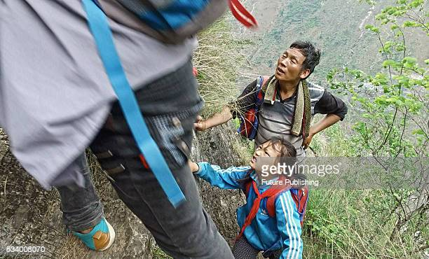 A man watches children of Atule'er Village climbing a cliff on their way home in Zhaojue county in southwest China's Sichuan province on May 14 2016...
