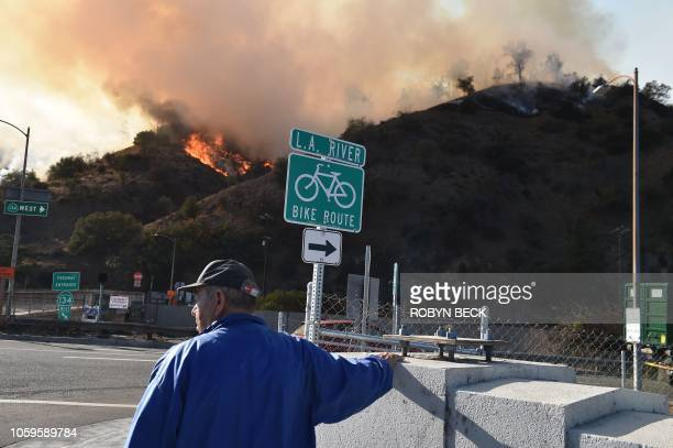 A man watches flames from a wildfire in Griffith Park in Los Angeles California November 9 2018 Staff at the Los Angeles Zoo which is located in the...