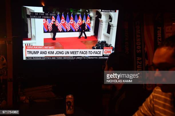 A man watches footage of North Korea's leader Kim Jong Un meeting with US President Donald Trump during the USNorth Korea summit in Singapore on a...