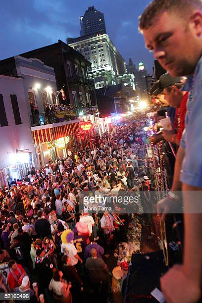 A man watches from a balcony as revelers walk on Bourbon Street during Mardi Gras festivities February 8 2005 in New Orleans Louisiana Mardi Gras is...