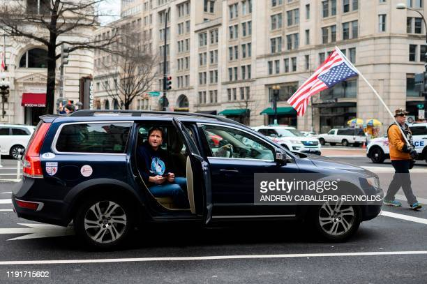 A man watches from a car as antiwar activist demonstrate outside the Trump International Hotel in Washington DC on January 4 2020 Demonstrators are...