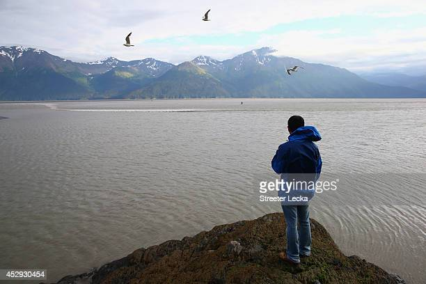 A man watches from a rock as surfers catch the Bore Tide at Turnagain Arm on July 16 2014 in Anchorage Alaska Alaska's most famous Bore Tide occurs...
