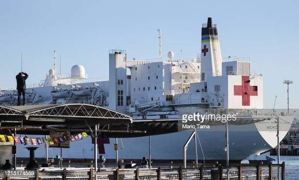 A man watches from a roof as the USNS Mercy Navy hospital ship arrives in the Port of Los Angeles to assist with the coronavirus pandemic on March 27...