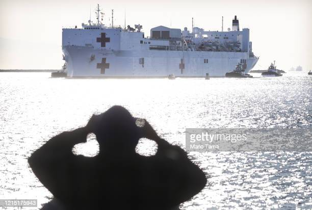 A man watches from shore as the USNS Mercy Navy hospital ship arrives in the Port of Los Angeles to assist with the coronavirus pandemic on March 27...
