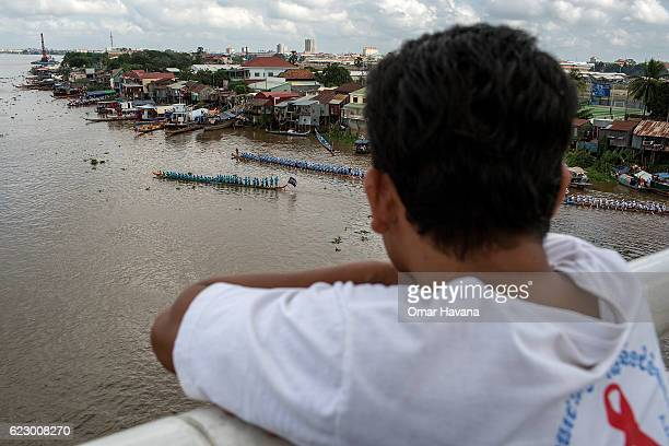 A man watches from the Japanese Bridge boat crews training on the morning of the first day of the Water Festival on November 13 2016 in Phnom Penh...
