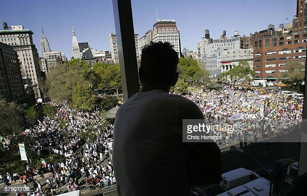 A man watches from the top floor windows of a department store a rally of thousands against proposed crackdowns on illegal immigrants May 1 2006 in...