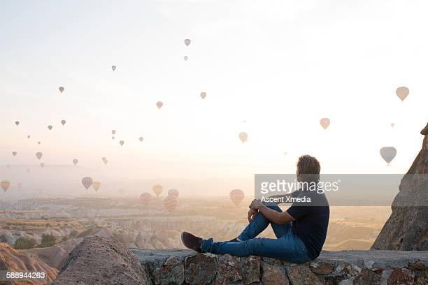man watches hot air balloons rise above desert - capadocia fotografías e imágenes de stock