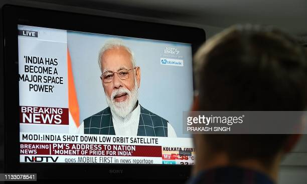 A man watches Indian Prime Minister Narendra Modi's address to the nation on a local news channel in New Delhi on March 27 2019 India on March 27...