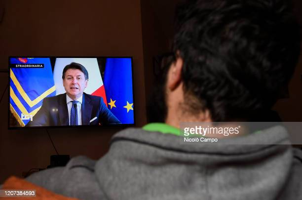 A man watches Italian Prime Minister Giuseppe Conte on TV announcing new economic measures to contain crisis caused by the coronavirus during an...