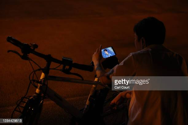 Man watches Japans mens semi-final match against Spain on a smartphone outside Saitama Stadium where the game is being played without spectators, on...