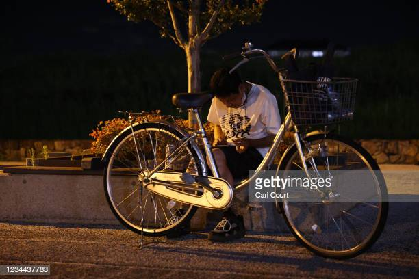 Man watches Japans men's semi-final football match against Spain on a smartphone outside Saitama Stadium where the game is being played without...