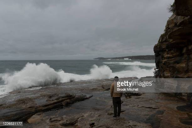 A man watches on as large waves hit the coast at La Perouse on May 23 2020 in Sydney Australia Winter weather including rain and strong winds is...