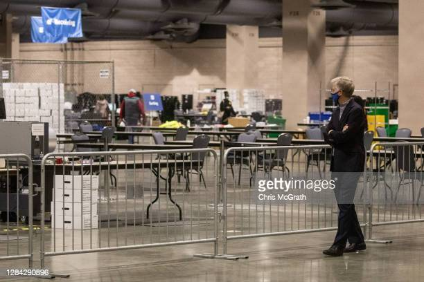 A man watches on from the observers area as election workers count ballots at the Philadelphia Convention Center on November 06 2020 in Philadelphia...