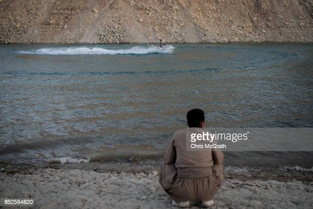 A man watches people use a jet ski ahead of the upcoming referendum for independence of Kurdistan on September 23 2017 in Sulaymaniyah Iraq The...