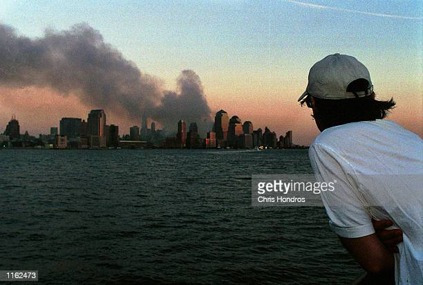 A man watches smoke emit from the former site of the World Trade Center September 12 2001 in Hoboken NJ Smoke filled the air all over lower Manhattan...
