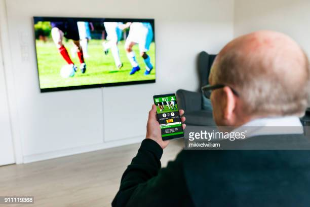 man watches soccer match on television and bets on the game with betting app on phone - match sport stock pictures, royalty-free photos & images