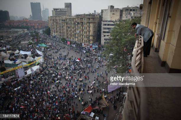 A man watches Tahrir Square protestors from a balcony on November 26 2011 in Cairo Egypt Thousands of Egyptians are continuing to occupy Tahrir...
