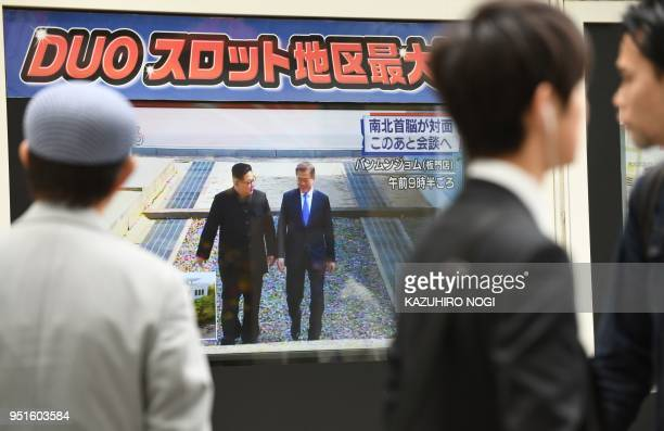 A man watches television footage of South Korean President Moon Jaein meeting North Korean leader Kim Jong Un in Tokyo on April 27 2018 North Korean...