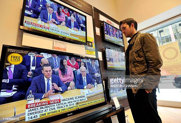 A man watches televisions in a shop in Glasgow Scotland on July 19 showing News Corporation Chief Rupert Murdoch giving evidence to a Parliamentary...